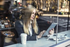 Business woman sitting in cafe and using tablet pc
